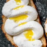slice of whipped ricotta toast drizzled in olive oil on a grey plate