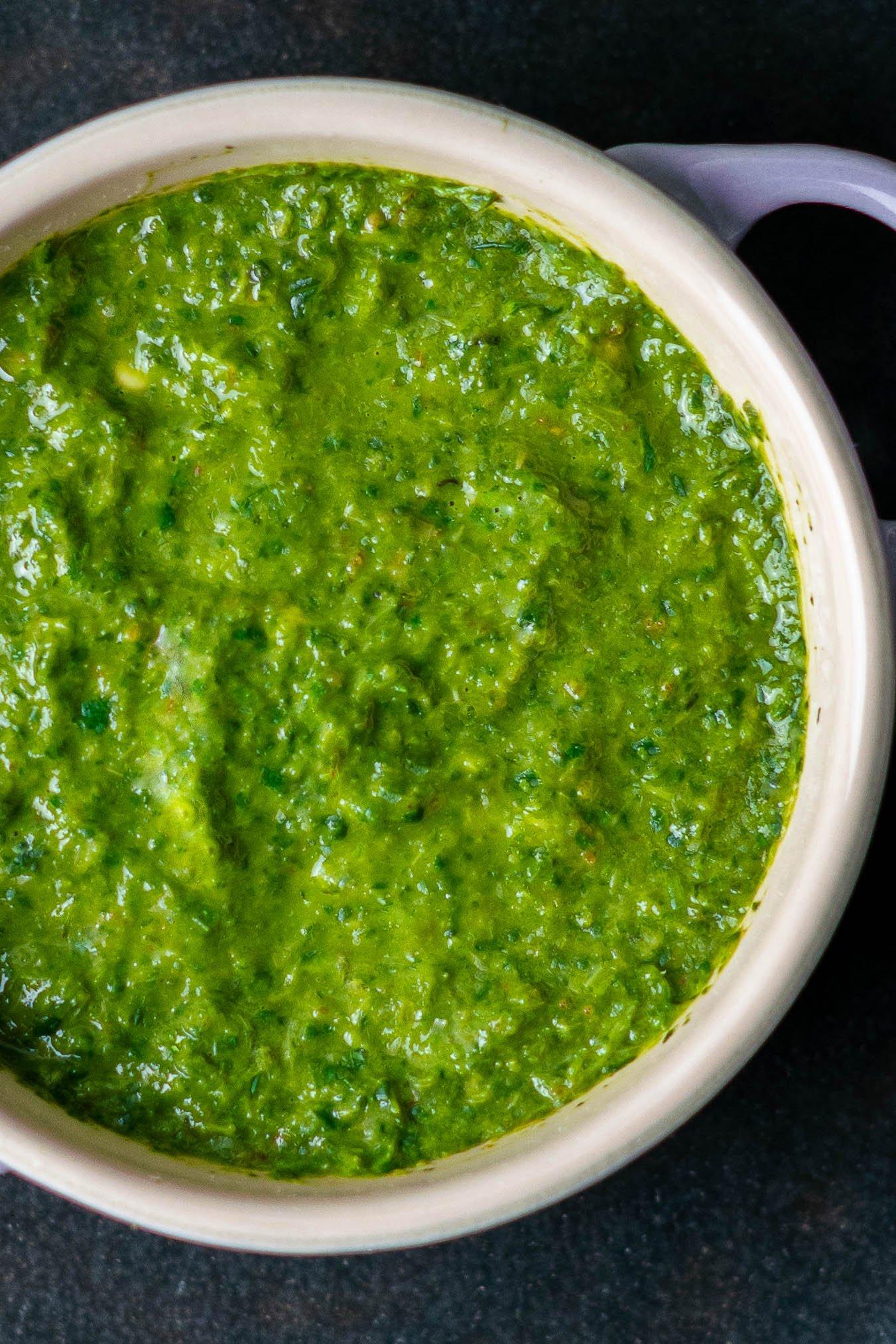 a close up of cilantro-mint chutney in a le creuset purple mini dutch oven