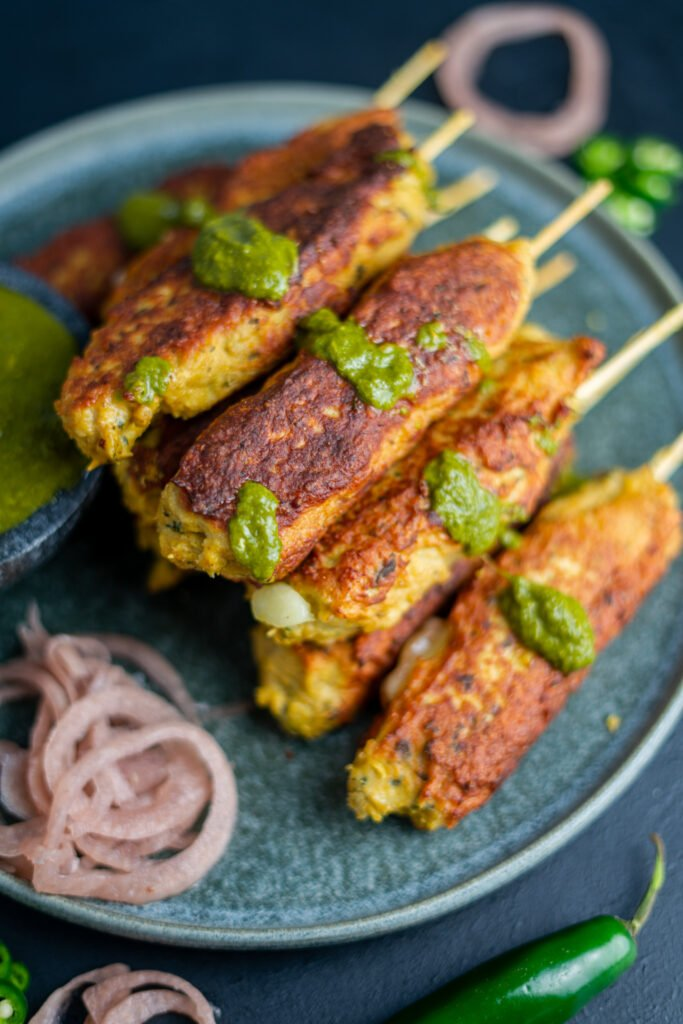a stack of chicken seekh kebabs with a drizzle of cilantro-mint chutney and pickled purple onions