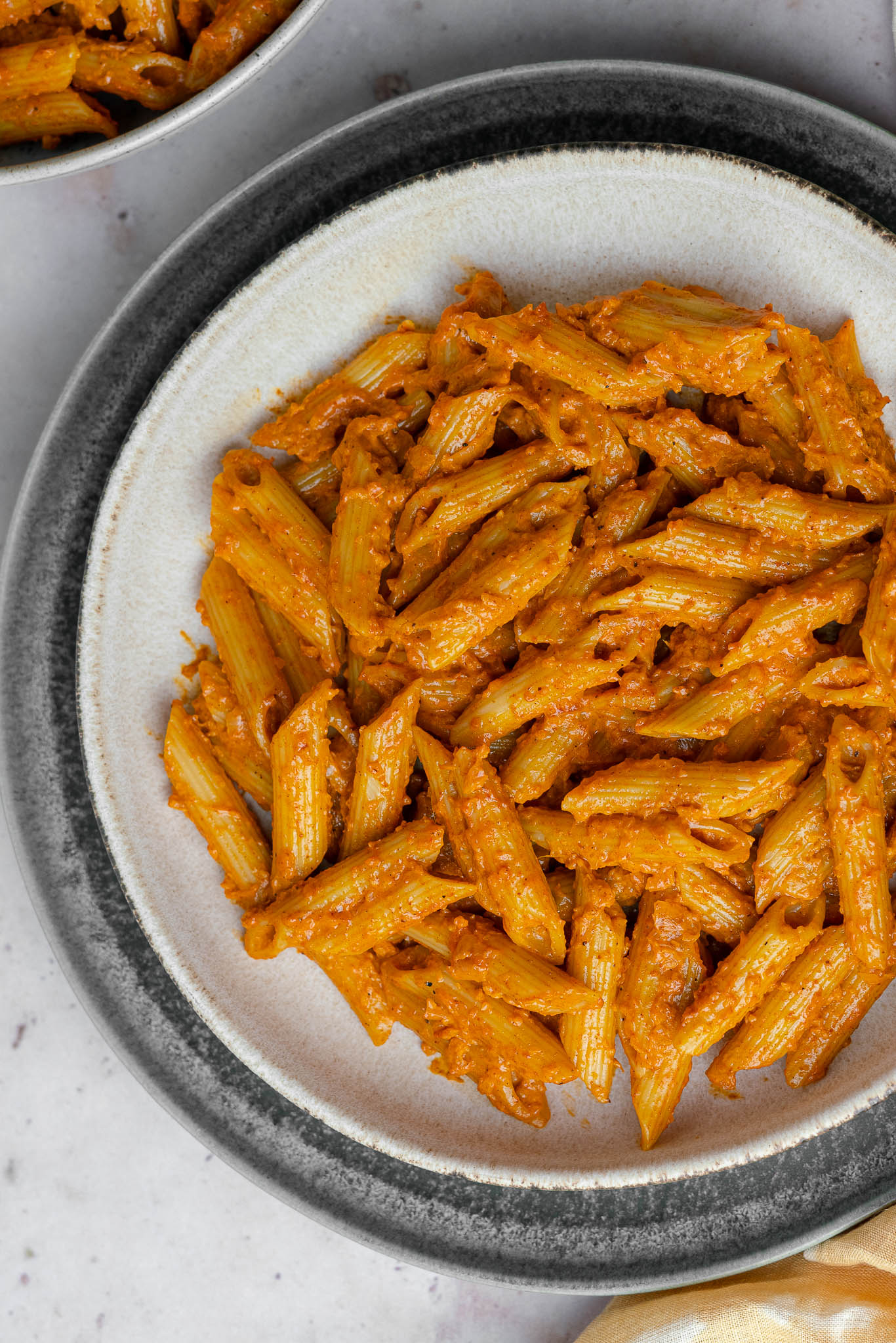 butter masala pasta half shot with pasta bowl nestled in plate