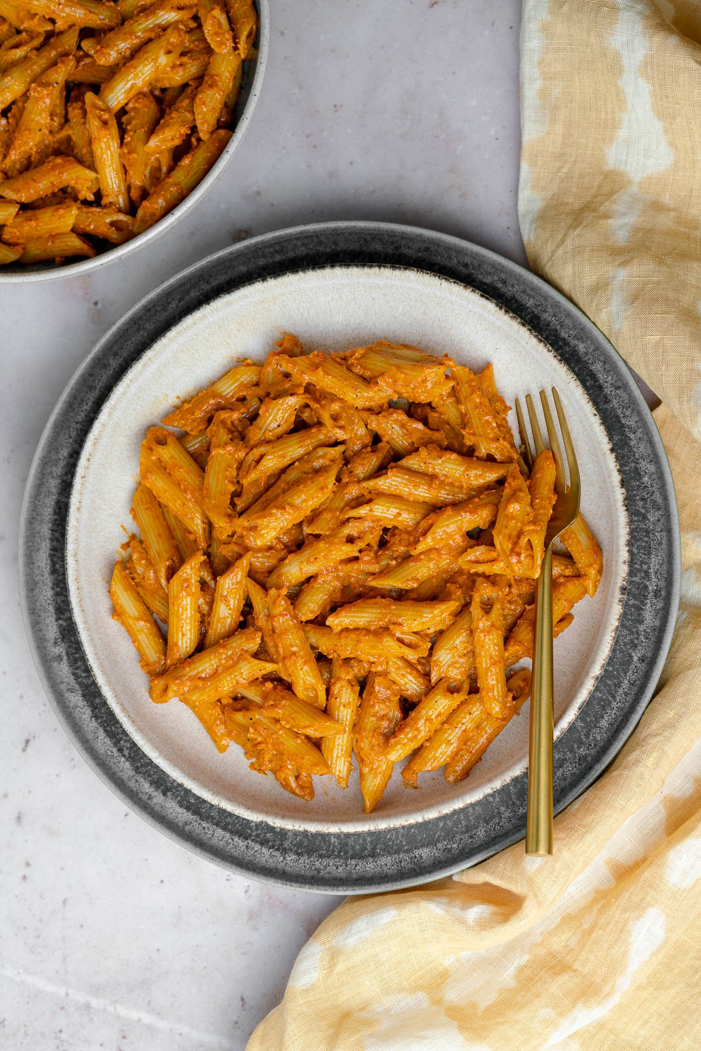 butter masala pasta in a pasta bowl with a golden fork