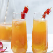 Tropical Guava Sangria in fluted glasses side by side with lychees, guava paste, and pitcher in the background
