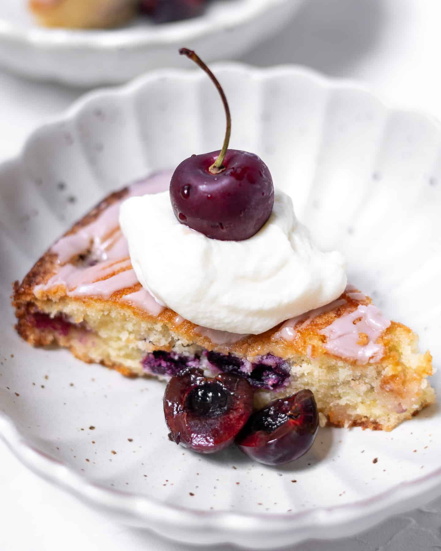 amaretto cherry almond cake in bowl with whipped cream and cherries
