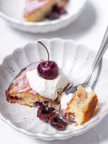amaretto cherry almond cake in bowl with whipped cream and cherries dug into with a spoon