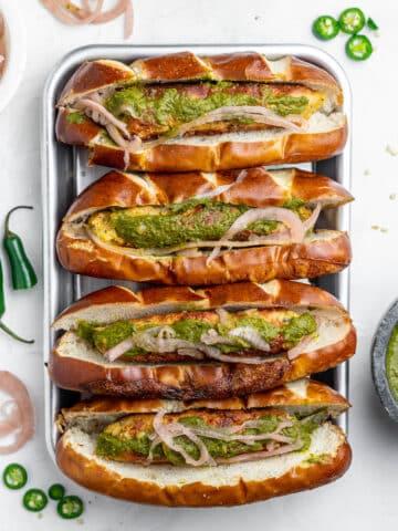 four seekh kebab rolls with chutney, pretzel buns, and pickled onion in a tray