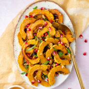Delicata Squash with Pomegranates, Walnuts, and Basil in a platter with a golden spoon and honey in a bowl