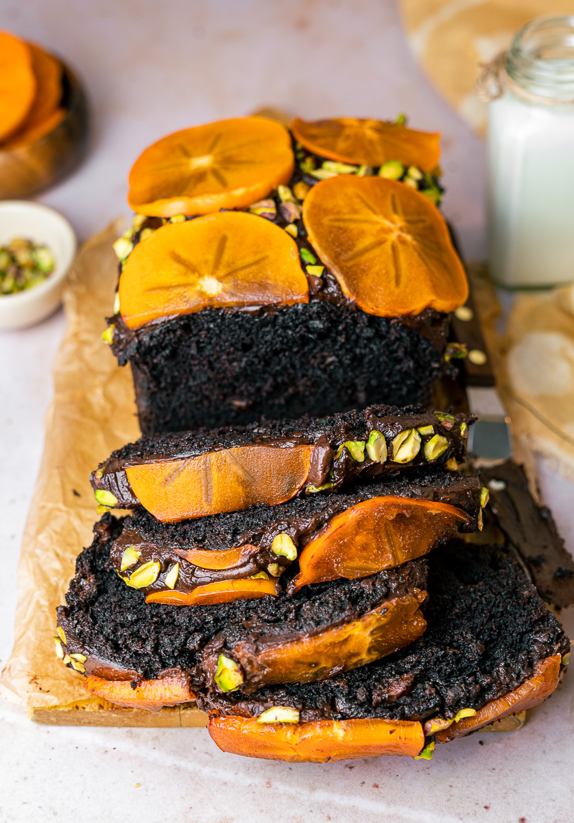 Four Persimmon Chocolate Loaf Cake Slices with milk, persimmon slices, and pistachios