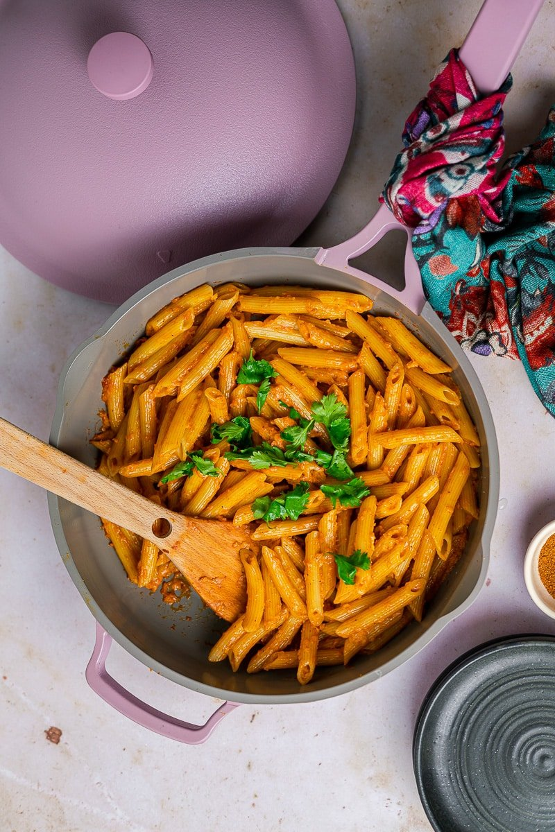 Butter Masala Pasta in a lavender always pan with cilantro garnish and a wooden serving spoon