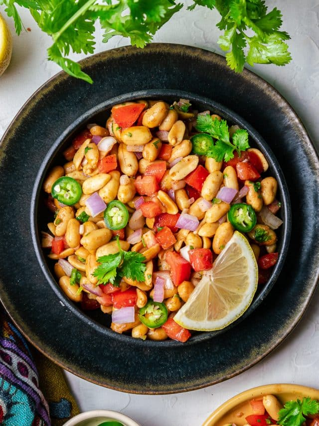 Peanut chaat in black bowl with lemon and cilantro