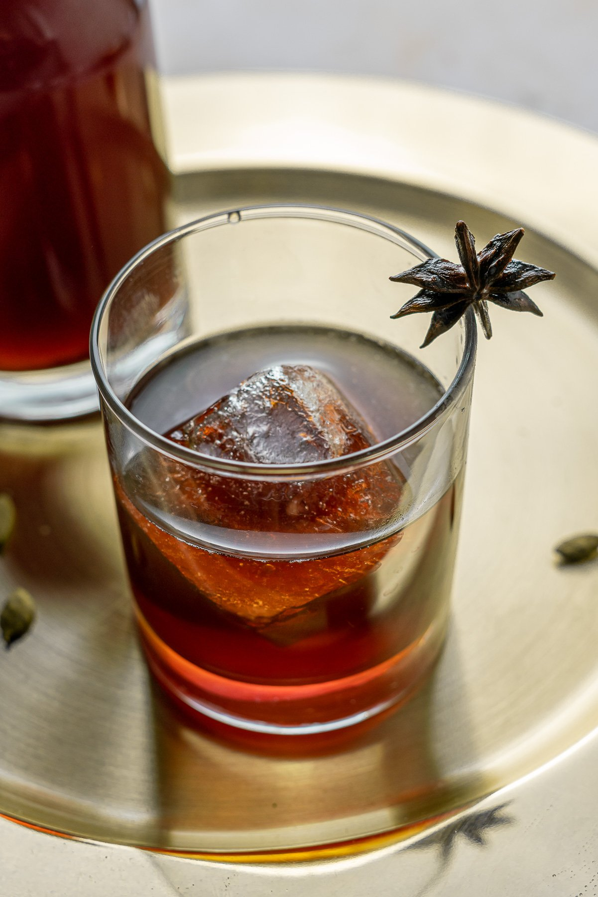 Chai Liqueur in glass with star anise garnish with bottle on a Gold Plate