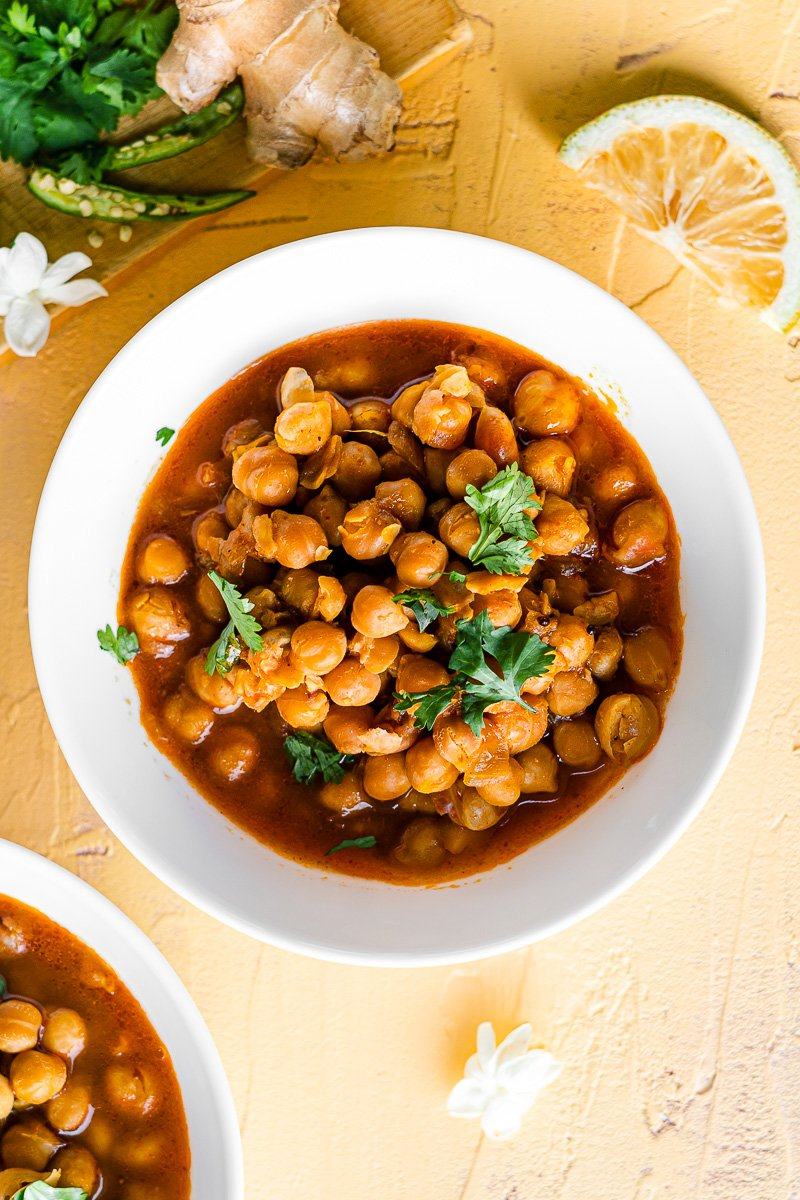 chole in a white bowl with lemon wedges