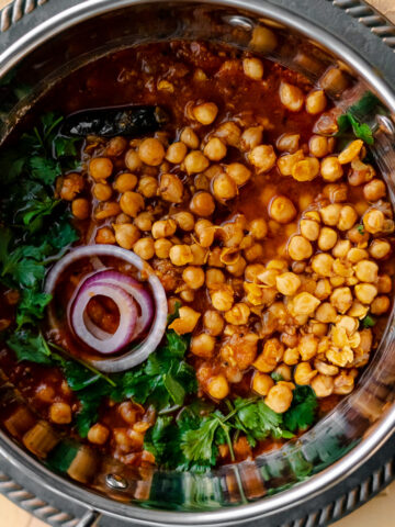 close up shot of chole in a flat bottomed wok with red onion and cilantro garnish