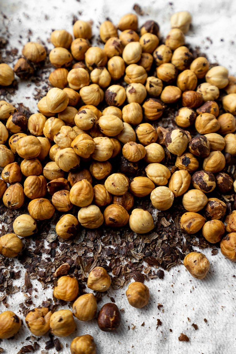 Skinless roasted hazelnuts in pile on towel with skin rubbed off