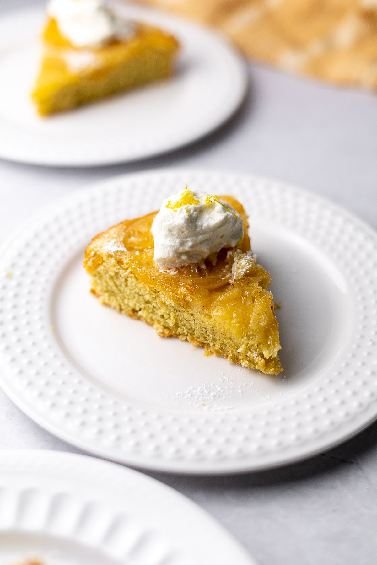 two slices of lemon cardamom olive oil cake with whipped cream
