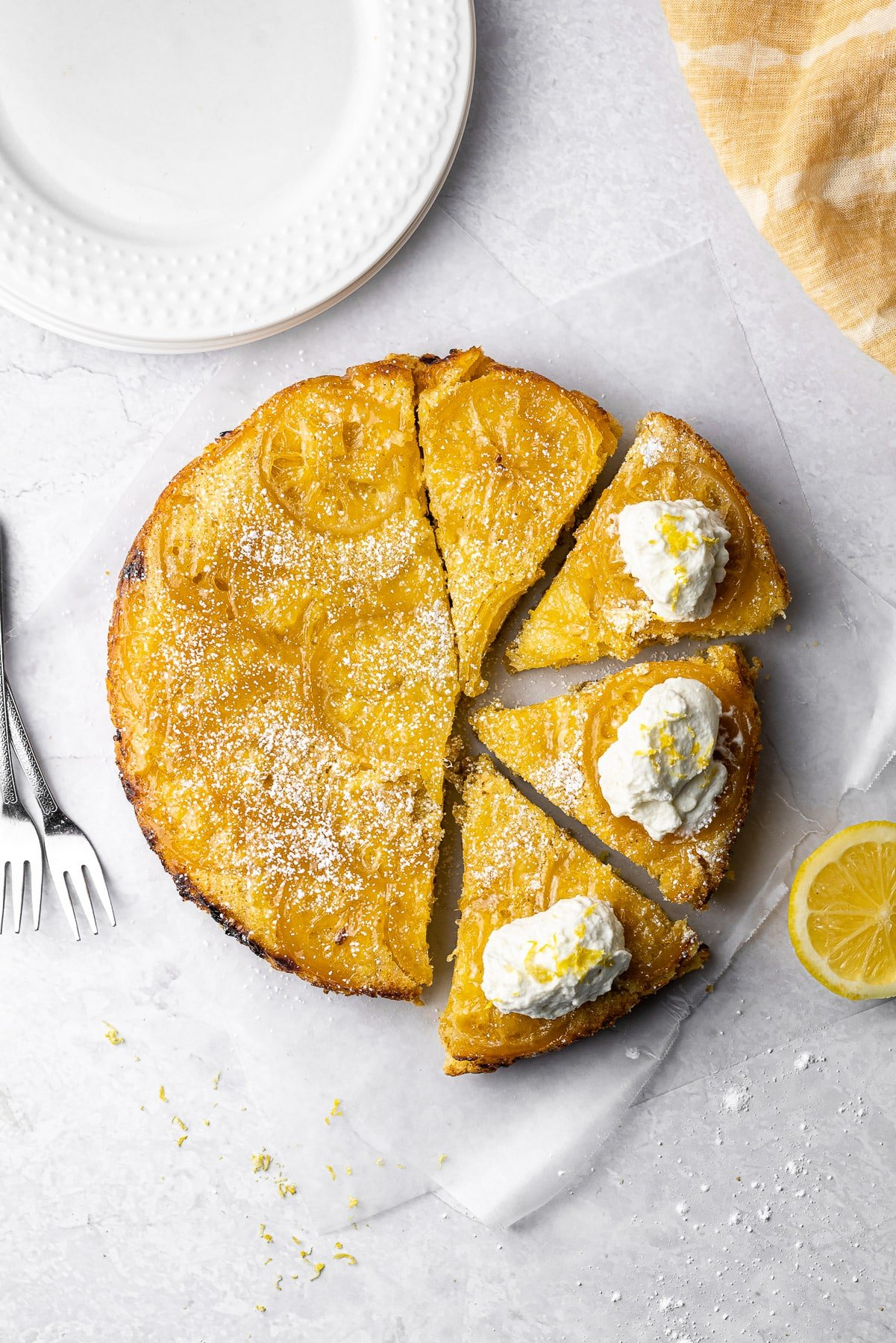 lemon cardamom olive oil cake sliced into four pieces. three of them have whipped cream and lemon zest