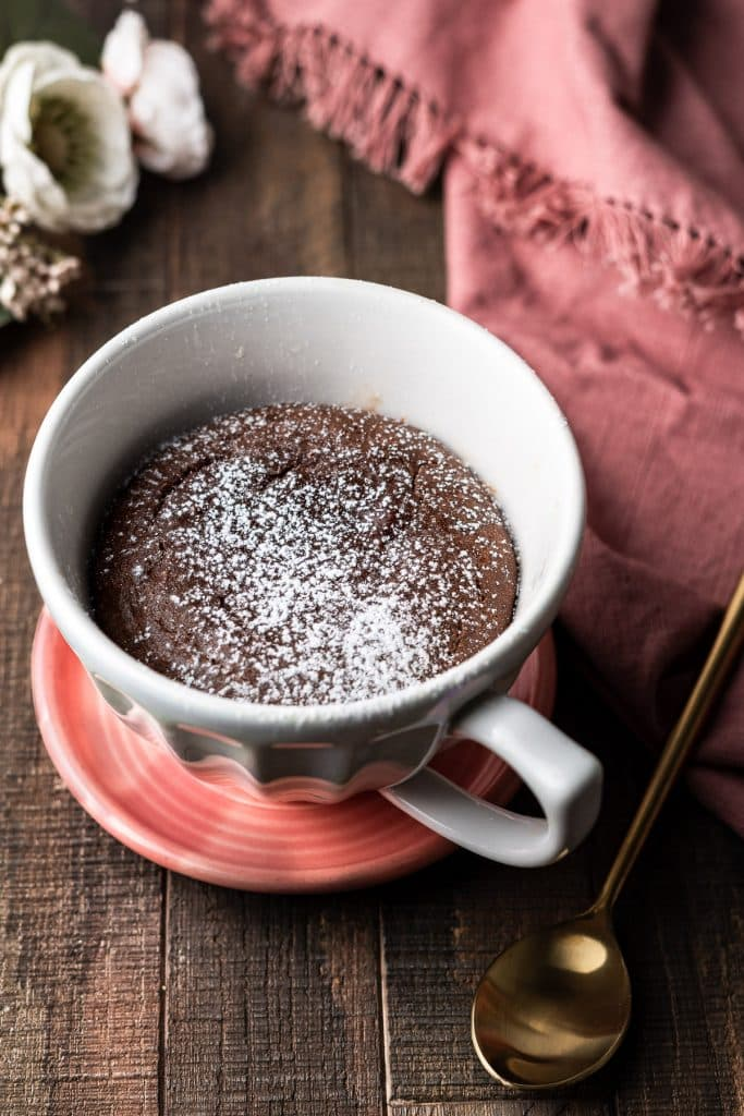 Nutella Lava Mug Cake in a mug on a plate with a spoon