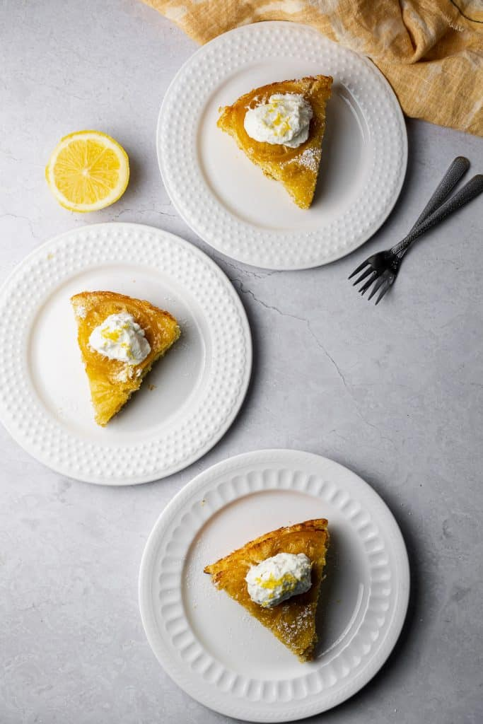 Three Lemon Cardamom Olive OIl Cake Slices on an s-curve with cake forks and a lemon half