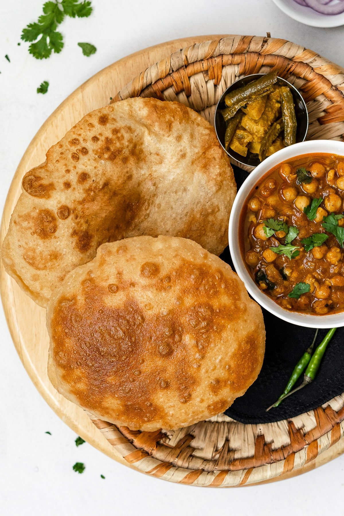 two fried bhature with chole and achaar