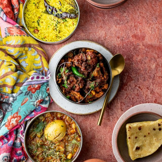 a spread of indian food with rice, roti, chicken, and egg curry