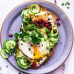 egg, cucumber, pomegranates, halloumi, chives, and labneh on homemade toast on a purple plate