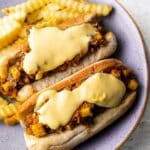 a close up at a 45 degree angle with paneer filling in a hot dog bun with cheese sauce and fries on the side