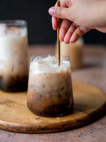 Mixing shaken espresso into oat milk