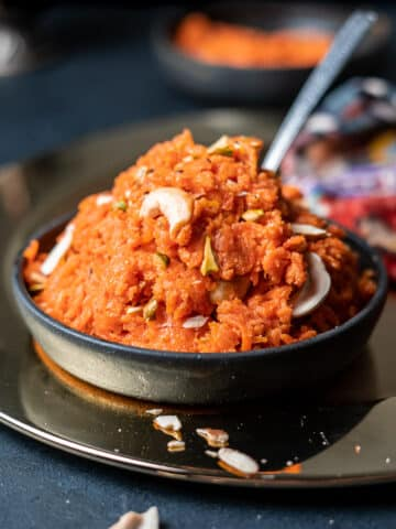gajar ka halwa in a black bowl on a charger with a spoon sticking out of it and almond slivers