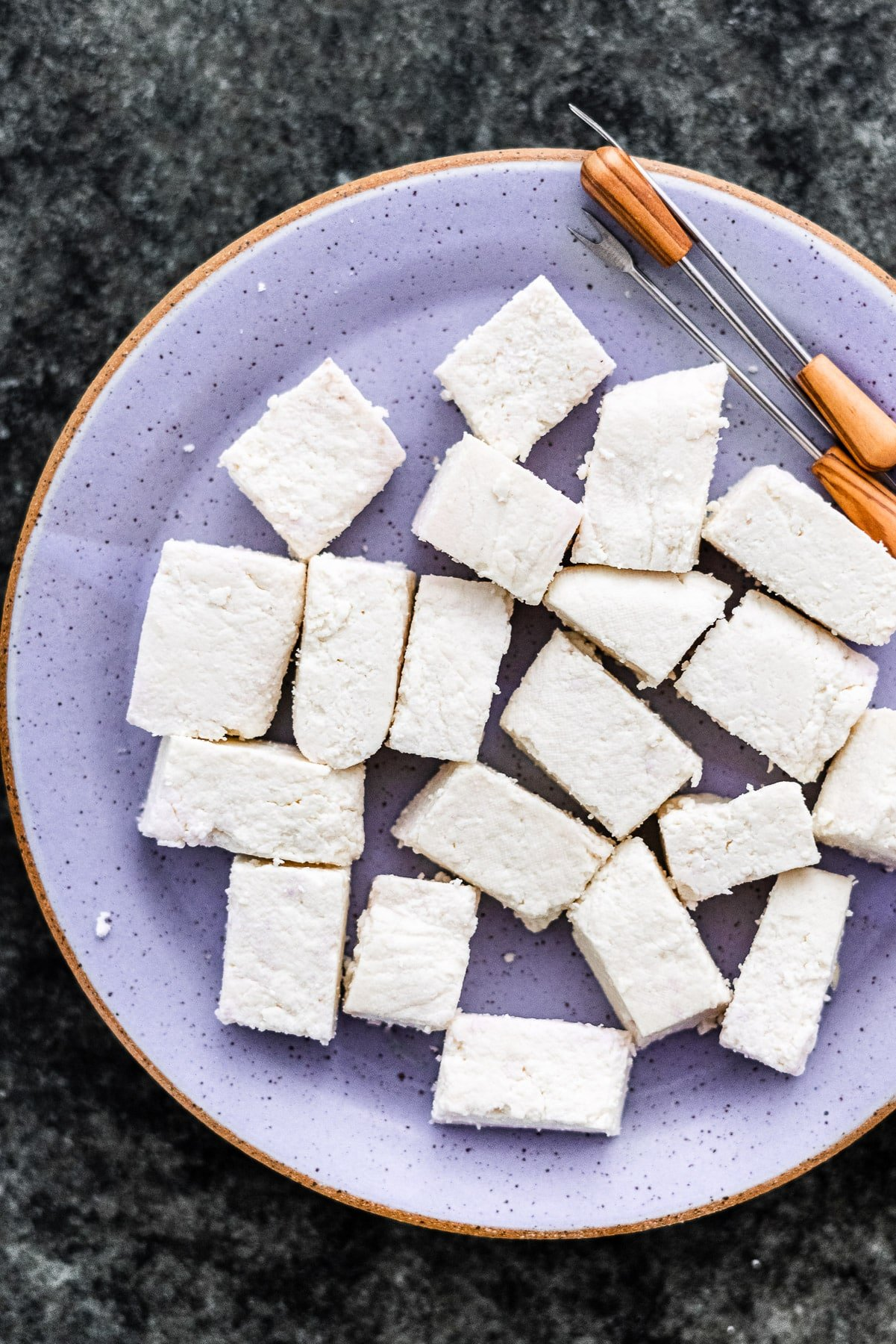 homemade paneer cut up in rectangles on a plate with appetizer picks