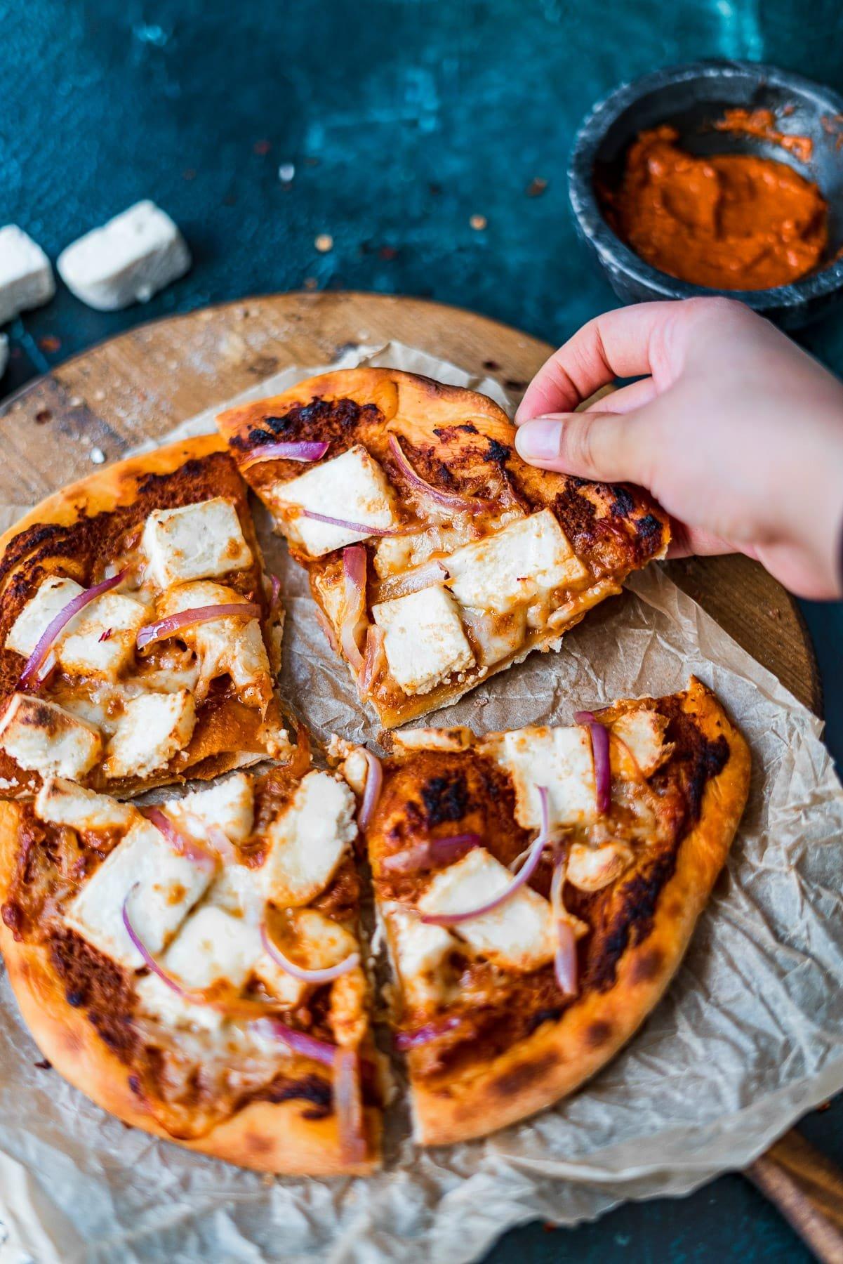 a hand grabbing a slice of paneer makhani pizza
