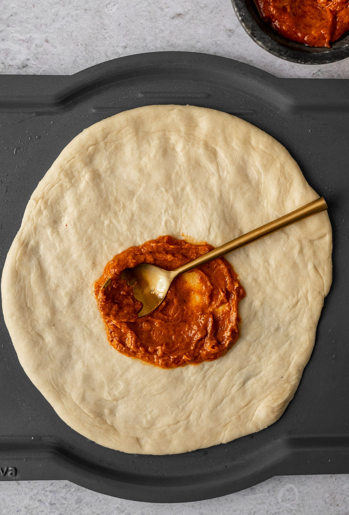 pizza dough on a brava tray with makhani sauce spread by a spoon