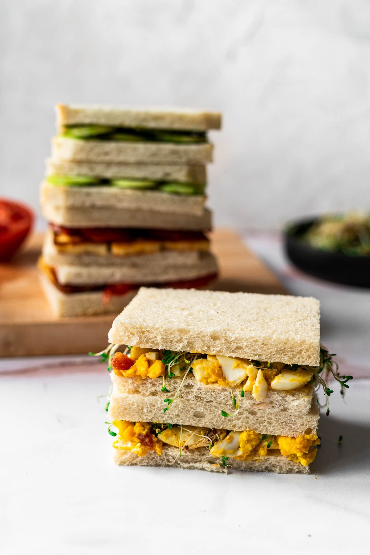 chutney egg salad tea sandwich in the forefront of the photo with stacked tea sandwiches in the back