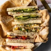 three tea sandwiches sliced into diagonals and stacked on top of each other in a bowl with yellow linen
