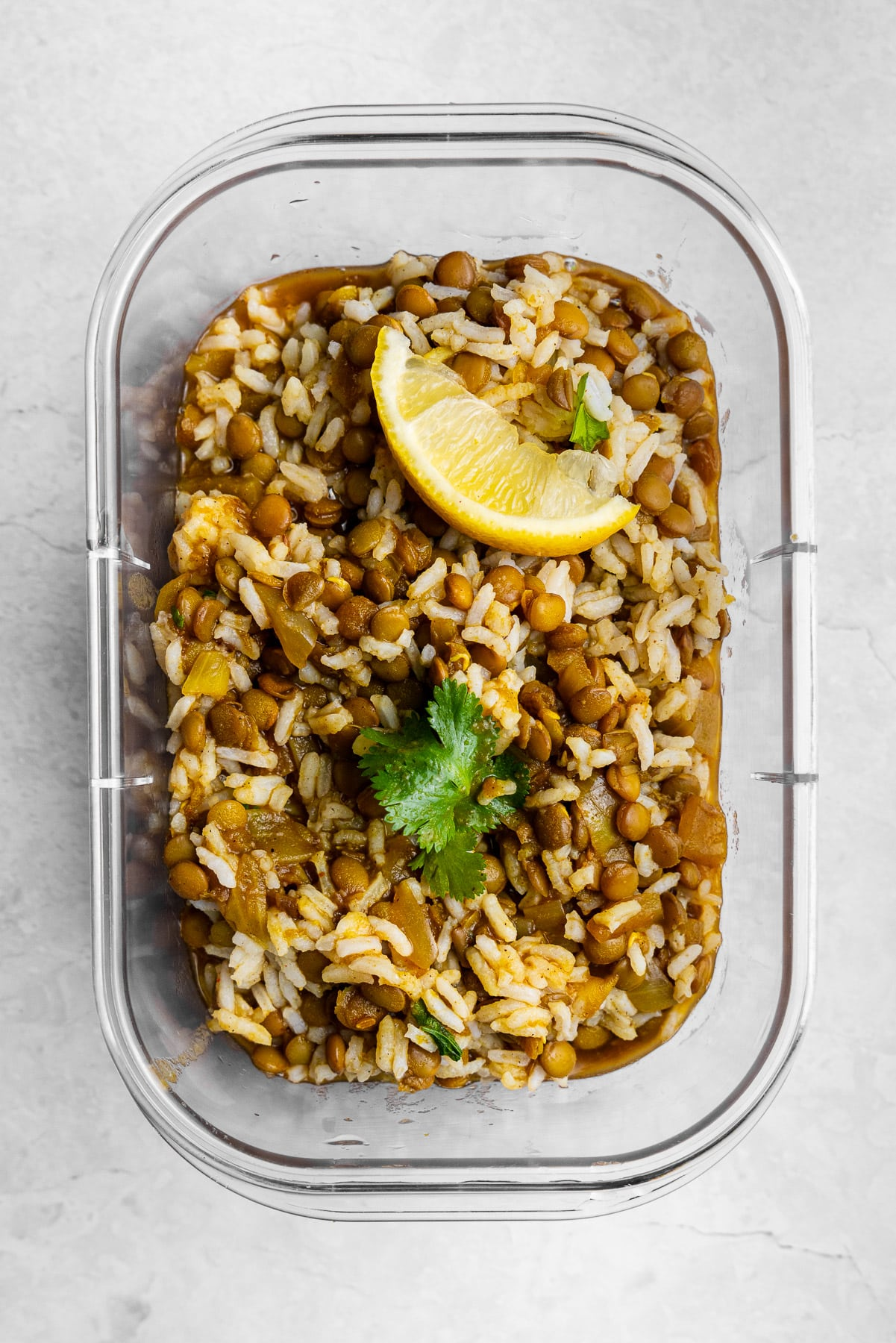 masoor dal mixed with rice, cilantro, with a lemon wedge in a meal prep container