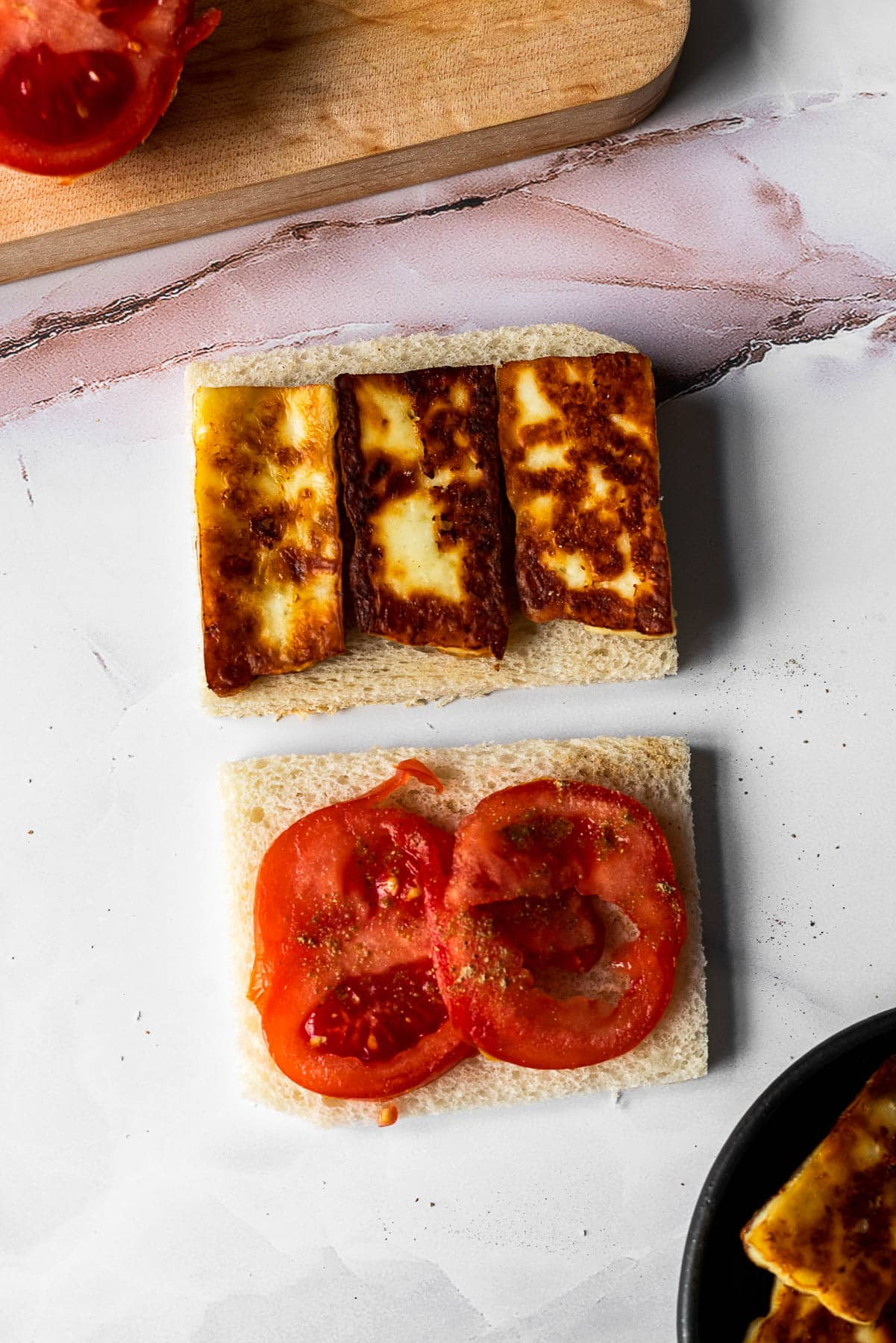 crustless white bread slices with fried paneer on one slice and tomato with chaat masala on the other slice