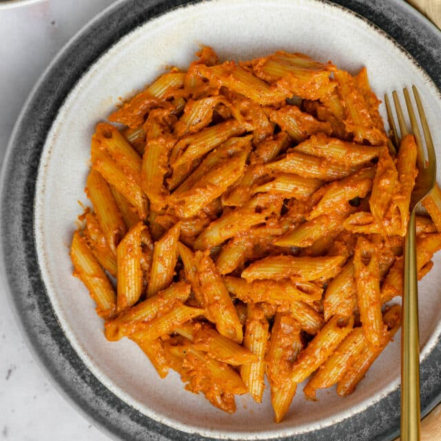 butter masala pasta in a white plate with a gold fork