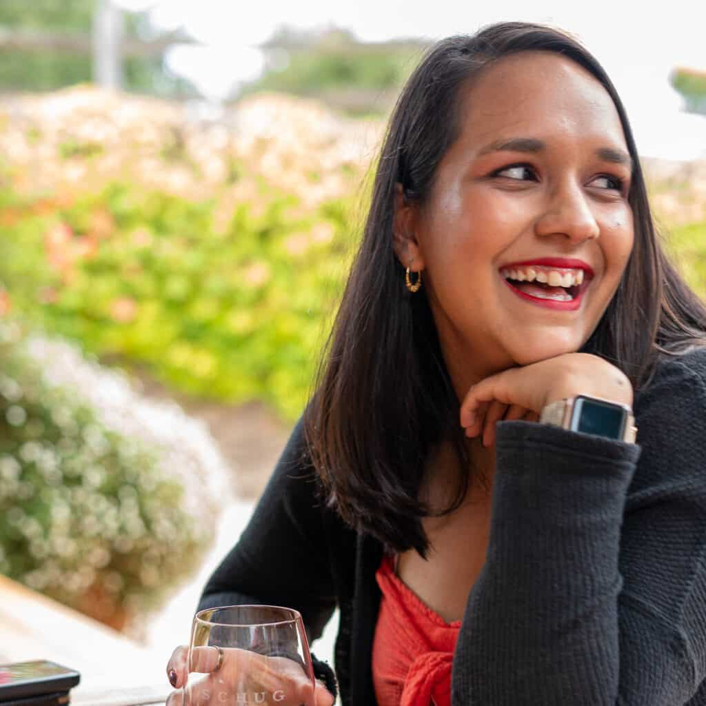 shweta smiling with a glass of wine at a winery