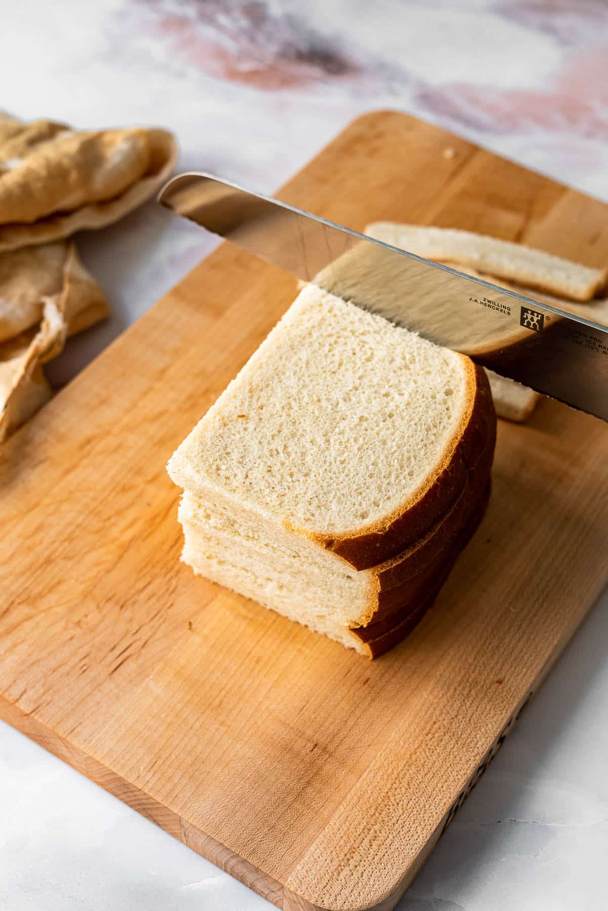 stack of white bread being sliced with a zwilling bread knife