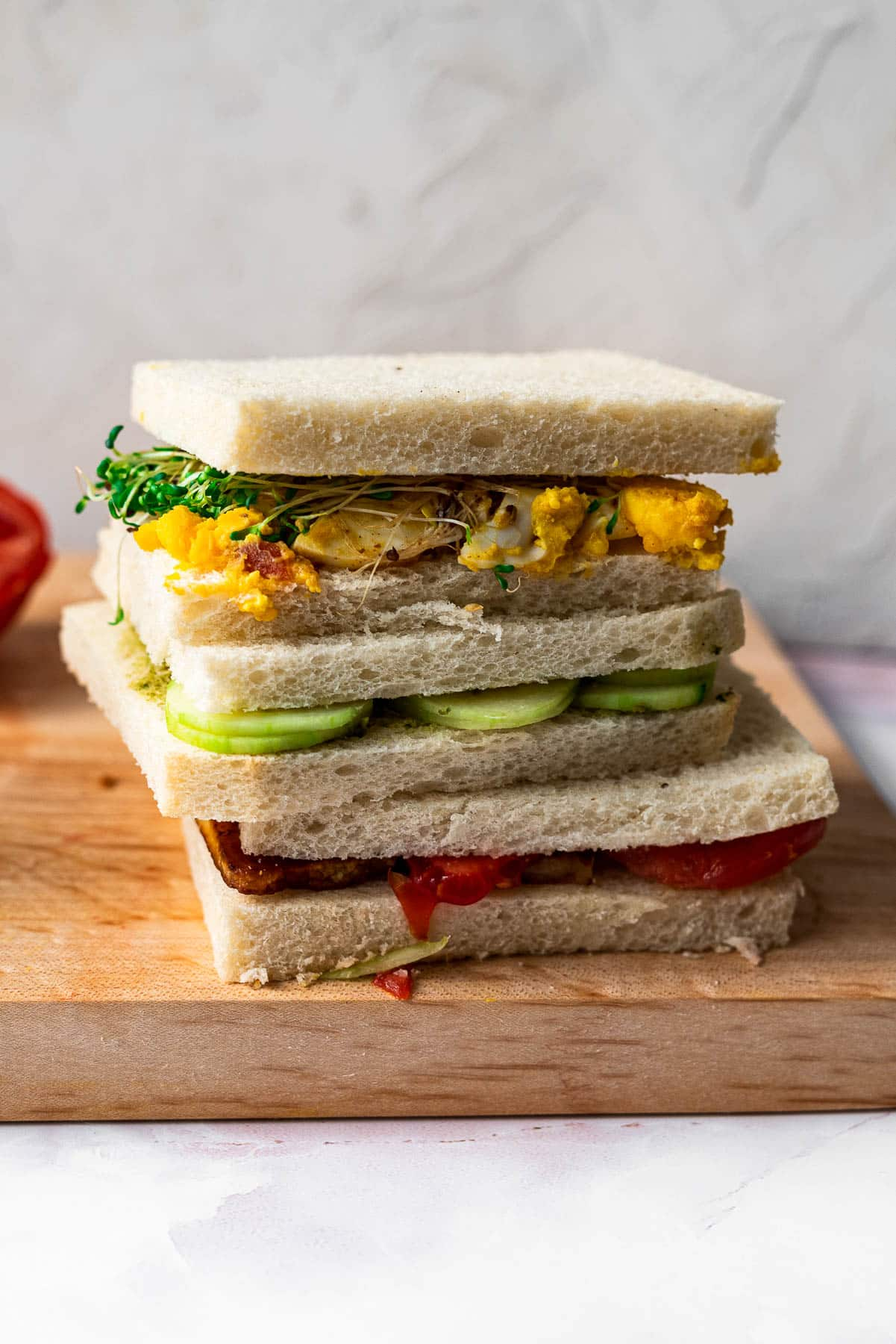 three tea sandwiches stacked on top of each other on a wooden board