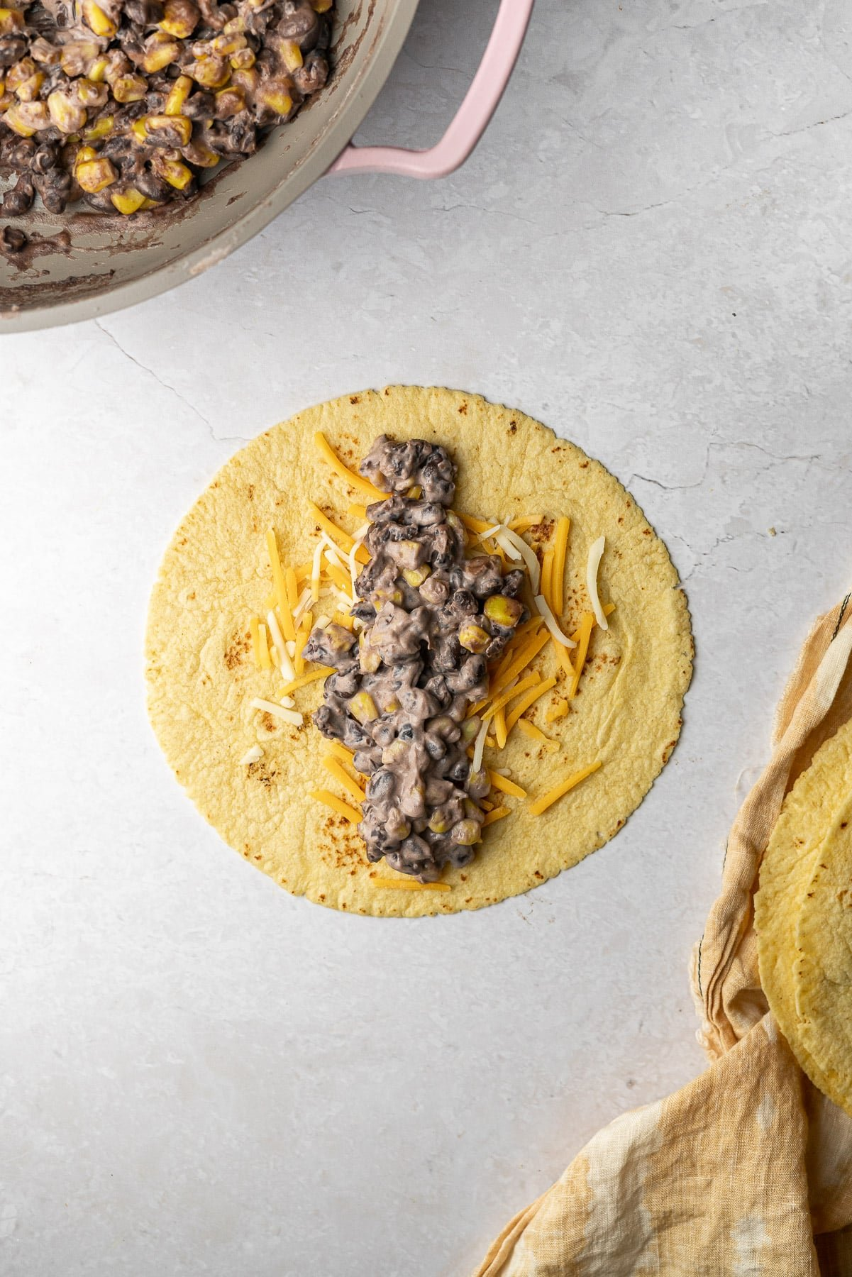 tortilla filled with shredded cheese and a cream cheese, corn, black bean filling