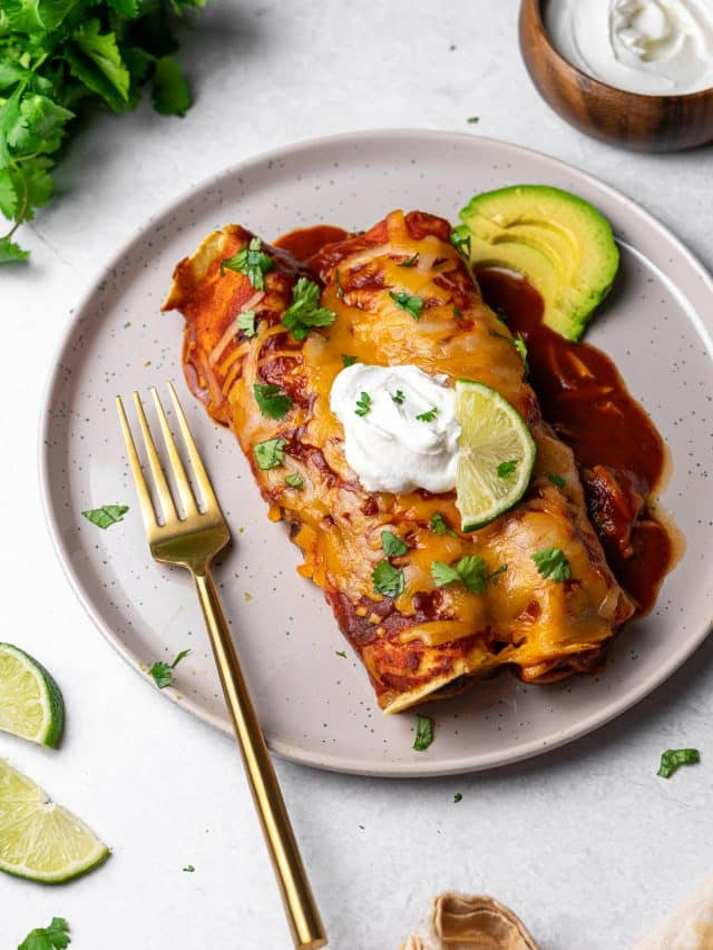 two enchiladas in a plate with sour cream, limes, cilantro, and avocado
