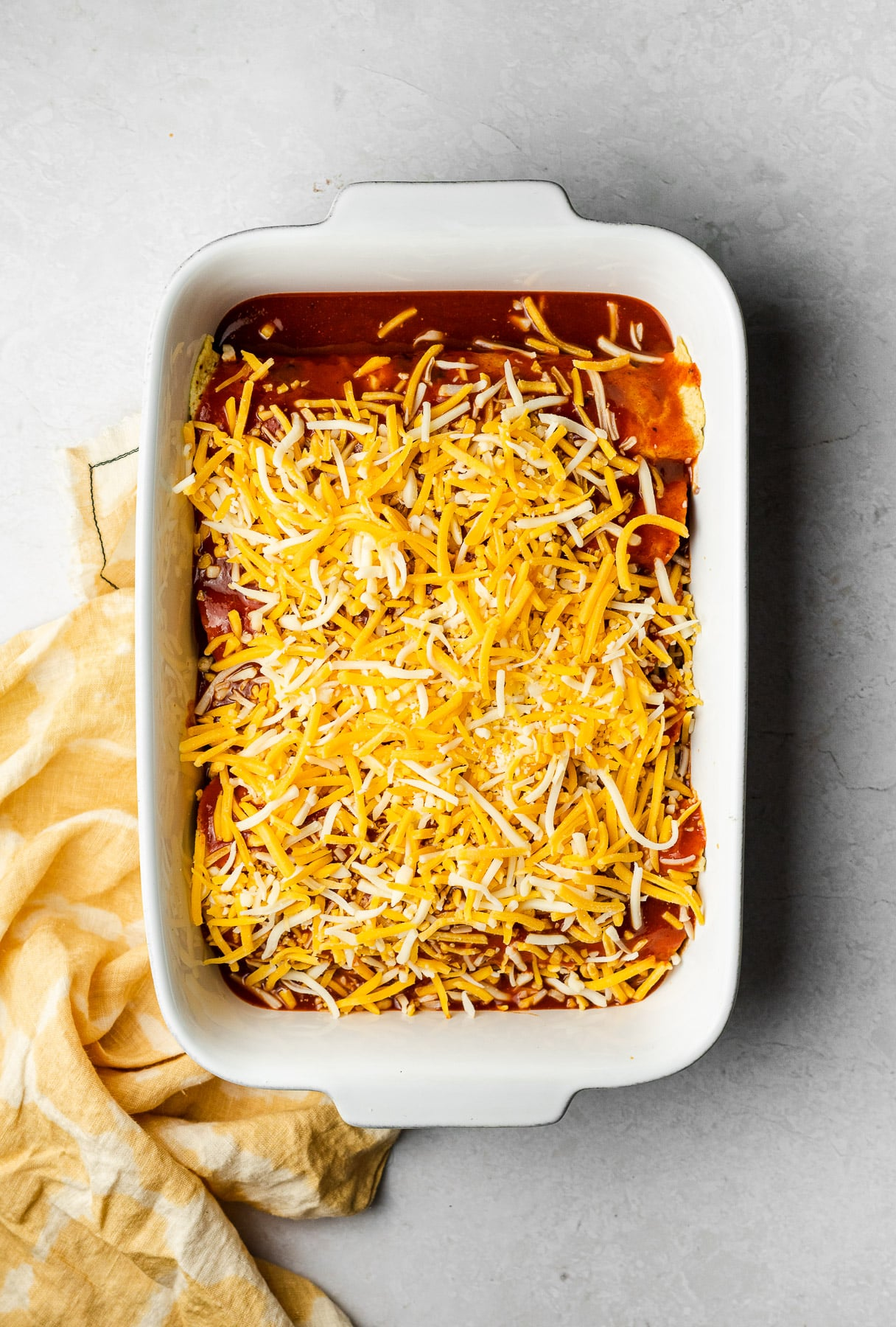 stuffed corn tortillas in a white baker topped with enchilada sauce and shredded cheese