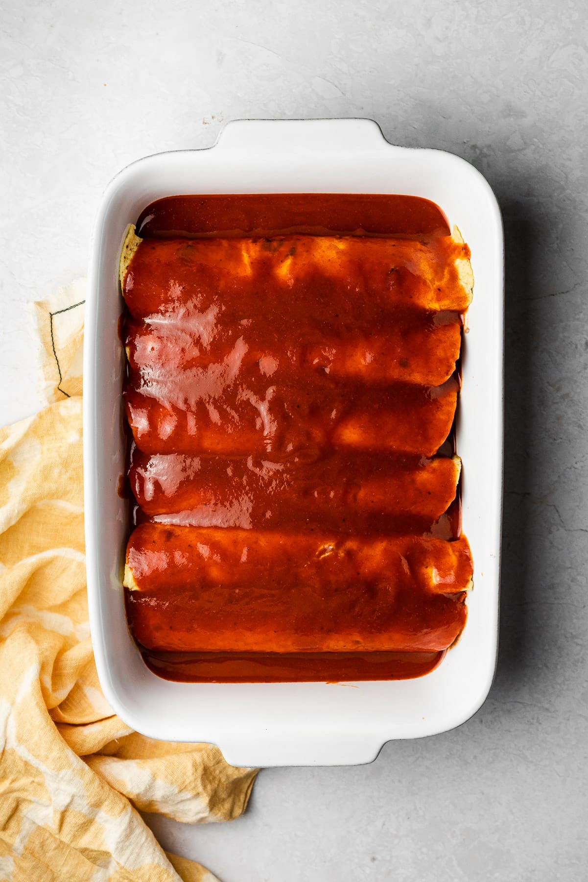 stuffed corn tortillas in a white baker topped with enchilada sauce