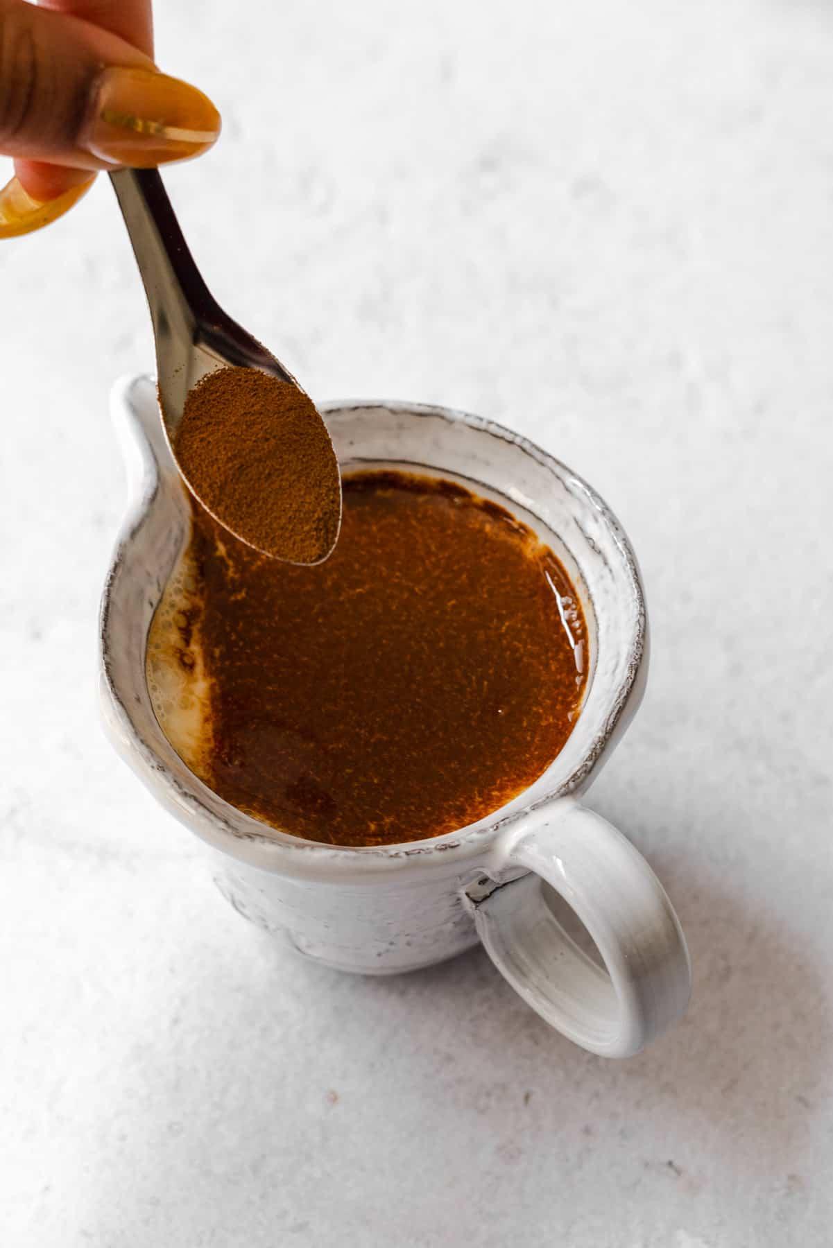 sprinkling espresso over a white pourer full of milk