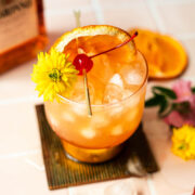 amaretto sour with bottle of alcohol in the back and garnishes next to it