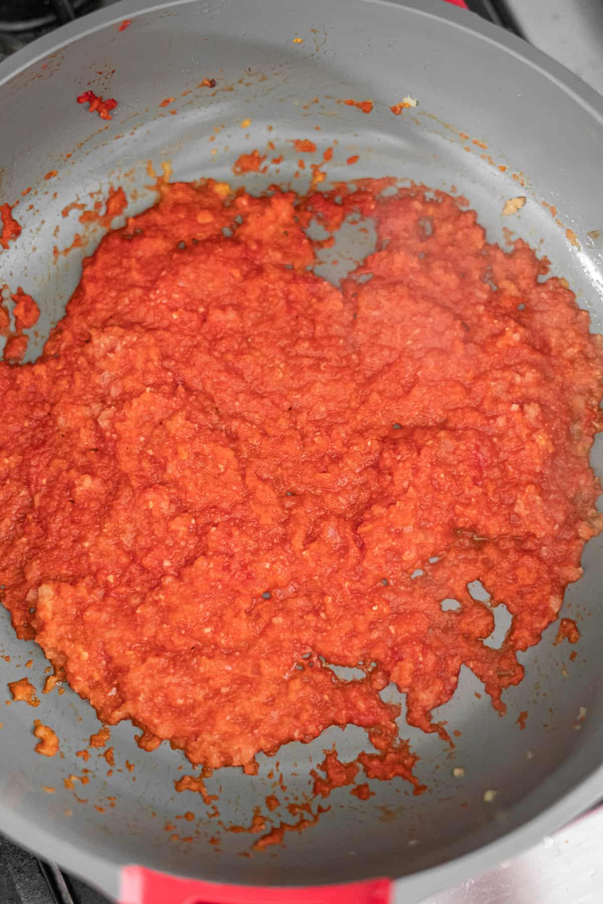 the onions, ginger garlic paste, and tomato paste, and masalas mixed together in a pan