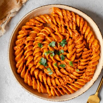 Colonne Pompei pasta covered in butter masala sauce in a pasta bowl with a gold fork