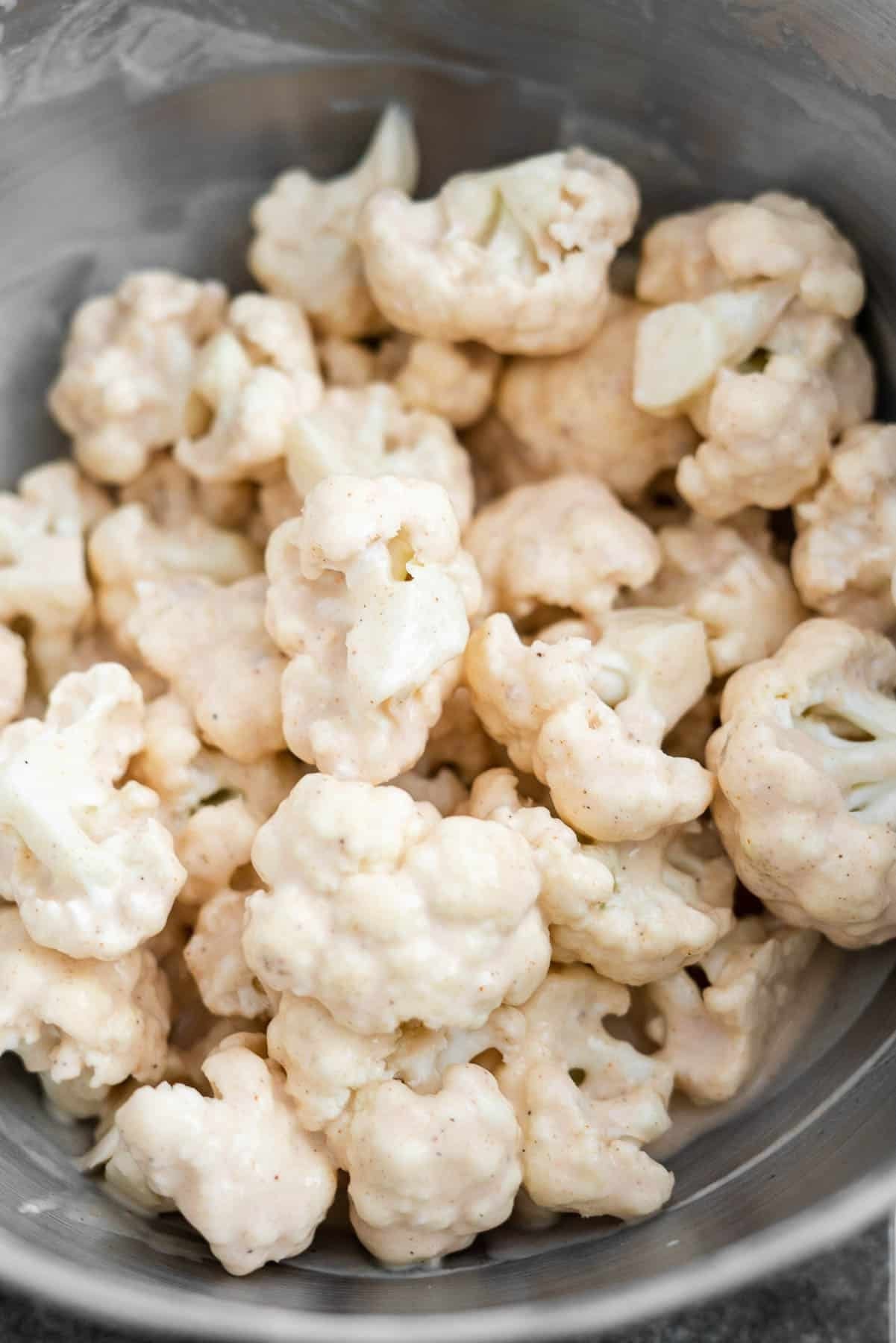 cauliflower florets covered in a spiced batter in a metal bowl