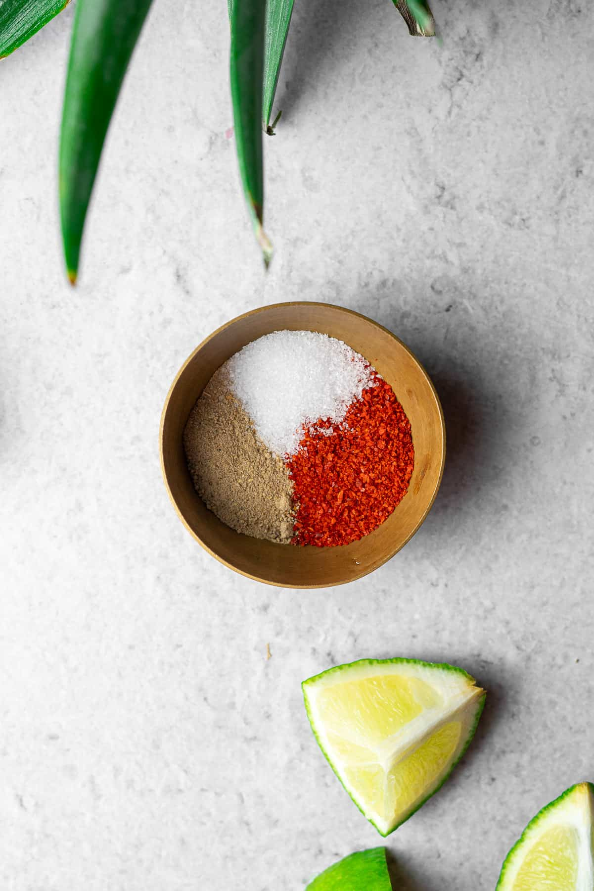 a small brass bowl with chili powder, chaat masala, and salt with limes and pineapple stem
