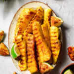 chili lime grilled pineapple in a platter with limes covered in spices