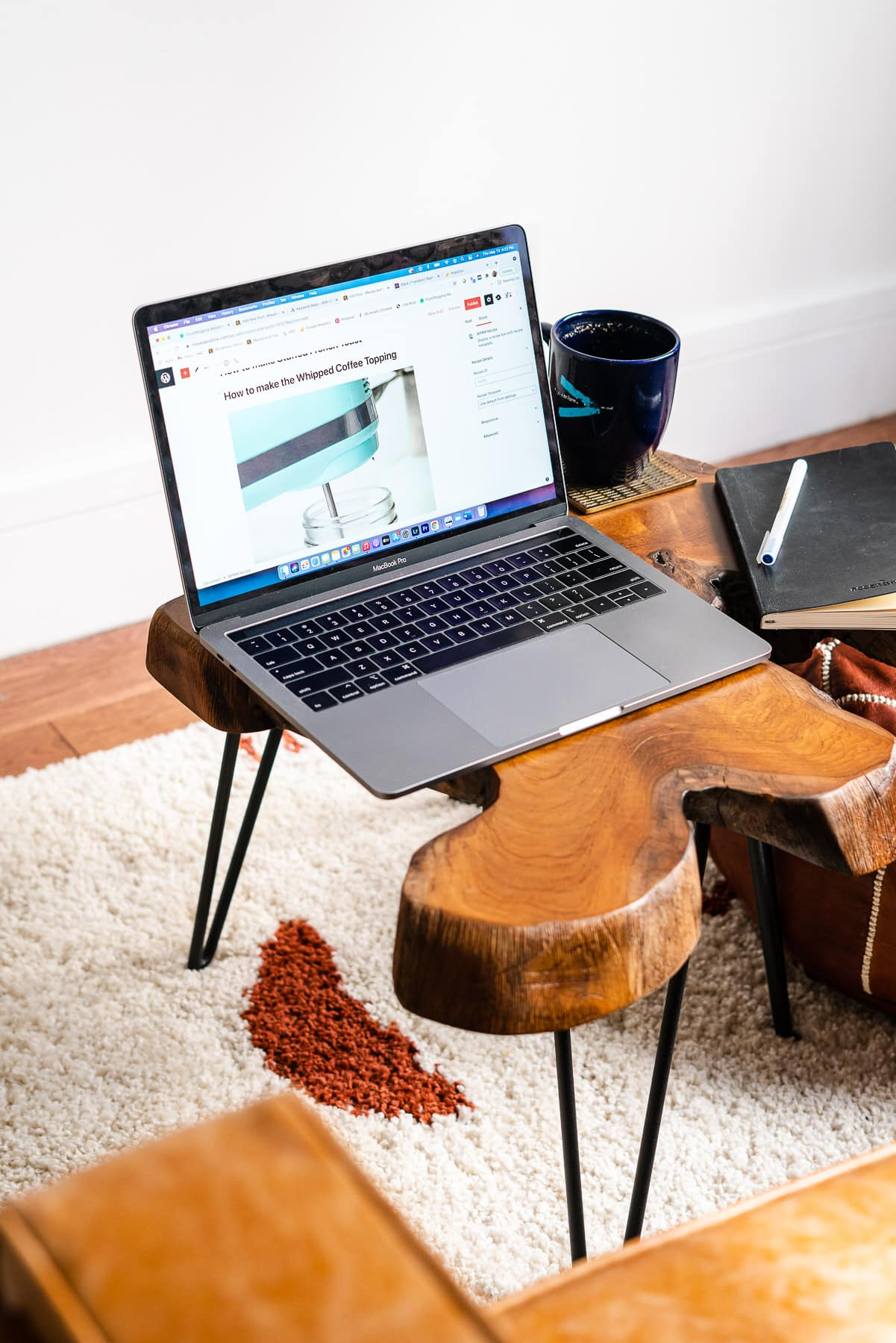 MacBook Pro with WordPress.org on the screen on a Wooden Slice table with tea and a notebook